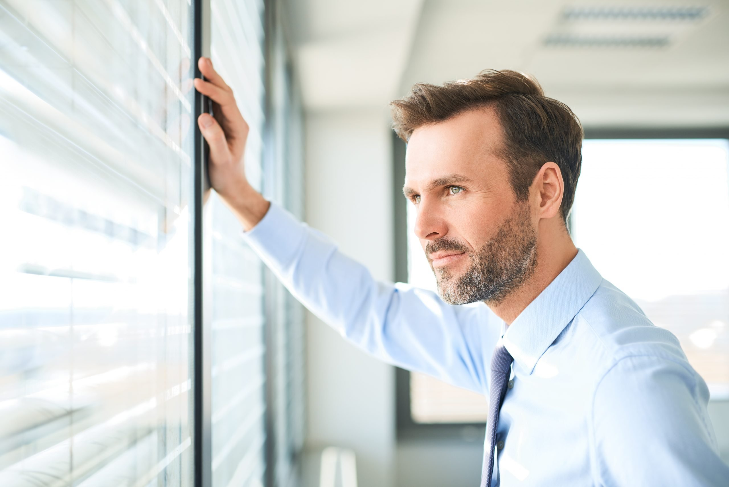 businessman looking through the window at office